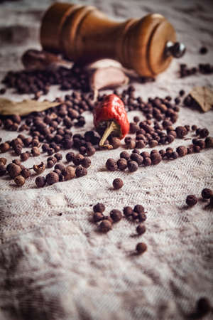 Close-up photo of the fruits of black pepper, red pepper and garlic on linen fabric Фото со стока