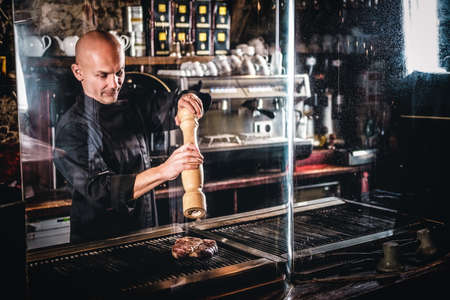 Master chef wearing uniform cooking delicious beef steak on a kitchen in a restaurant