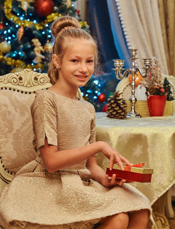 ute girl wearing a beautiful dress sitting on a chair and opens a gift box