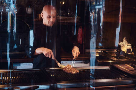 Chef cooking delicious beef steak on a kitchen, standing behind protective glass in a restaurant. Archivio Fotografico
