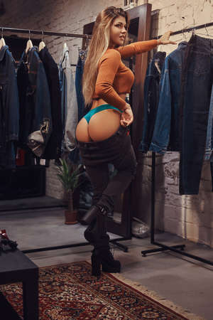 A beautiful girl with sagging pants posing in the fitting room of a clothing store.
