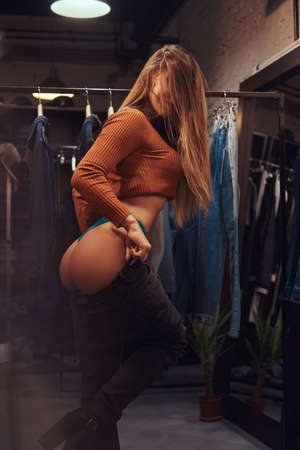 A sexy girl with hair covering face seductively pulling up pants in a fitting room of a clothing store