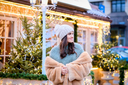 A beautiful girl wearing a winter hat and fur coat standing in evening street decorated with beautiful lights at Christmas time