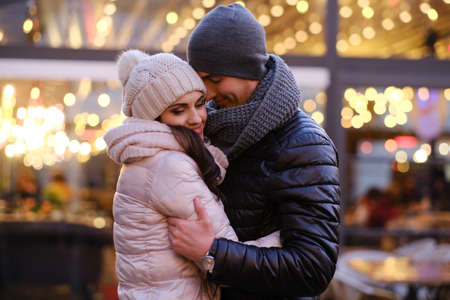 A young romantic couple wearing warm clothes hugging together in evening street near a cafe outside at Christmas time 版權商用圖片