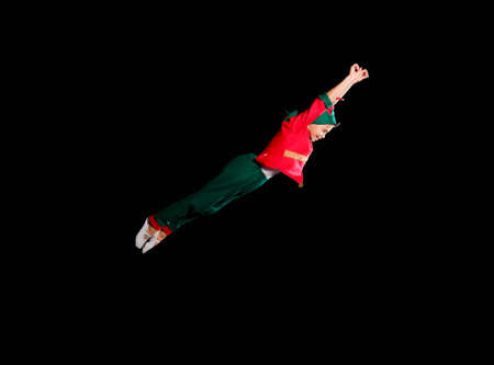 Christmas time, childhood, fairy tale. A young boy wearing elf costume is flying