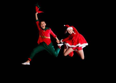 Weihnachtszeit, Kindheit, Märchen. Ein junges Mädchen im Weihnachtsmannkostüm und ein Junge im Elfenkostüm fliegen zusammen