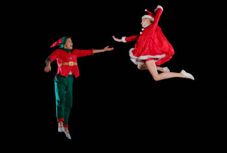 Christmas time, childhood, fairy tale. Cheerful kids - A young girl wearing a Santas costume and boy wearing elf costume flying together