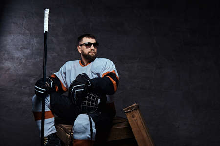Stylish bearded hockey player wearing full sports equipment and sunglasses sitting on wooden pallets.