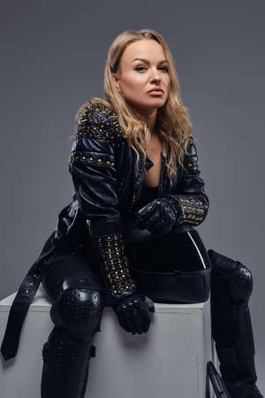 Portrait of a confident biker girl wearing racer costume sitting on a gray box in a studio.