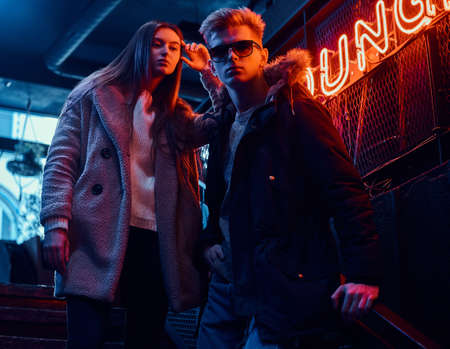 Stylish couple wearing warm clothes standing on the staircase to the underground nightclub, a backlit signboard in the background