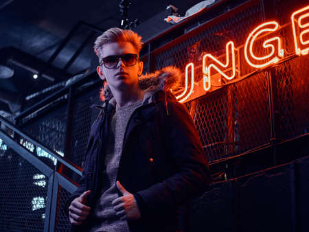 Young confident guy wearing coat with fur hood and sunglasses standing on the staircase to the underground nightclub, a backlit signboard in the background