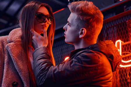 Portrait of a passionate young couple looking at each other in the underground nightclub with industrial interior, he gently touches her chin
