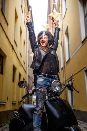 Cheerful hipster girl wearing a leather jacket and ripped jeans standing in a black classic scooter on the old narrow street Stock Photo