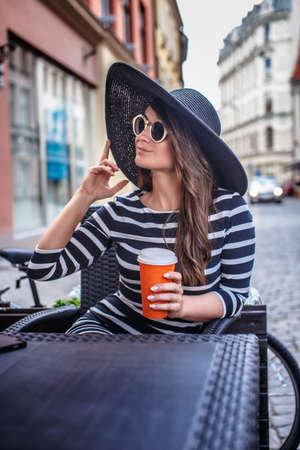 Portrait of a fashionable woman wearing sunglasses and stylish hat holding a cup of coffee while sitting in a summer street cafe. Stock Photo