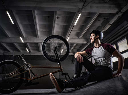 Young Bmx rider relaxing after practicing tricks with his bike in a skatepark indoors 免版税图像