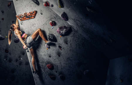 Young sporty woman climbing artificial boulder indoors.