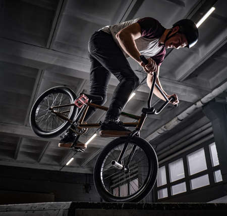 Professional BMX rider in protective helmet performing tricks in skatepark indoors Stock Photo