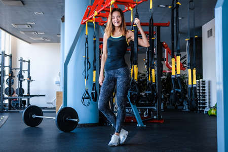 Cheerful girl wearing sportswear holding a suspension fitness straps