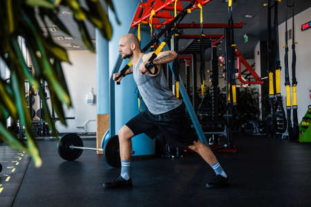 Tattooed athletic man exercising with suspension fitness rope in the gym