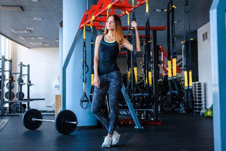 Joyful girl wearing sportswear holding a suspension fitness straps