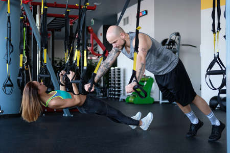 Couple workout in the gym, doing exercise with functional loops.
