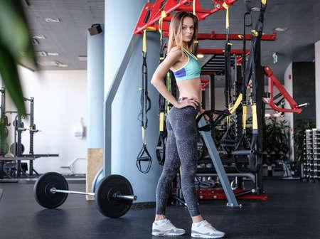 Girl in sportswear holding functional loops, posing in modern fitness club Standard-Bild