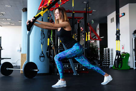 Slim fitness girl doing exercises with a suspension straps in a gym club.