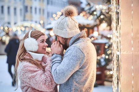 A happy young couple in love, man warming hands his girlfriend enjoying spending time together near a city Christmas tree. Holidays, Christmas, Wintertime.