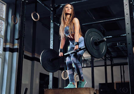 Athletic fitness woman wearing sportswear holding a barbell and posing while standing on a sports pedestal in a gym
