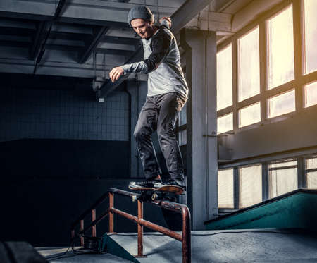 Skateboarder performing a trick on mini ramp at skate park indoor. Stock Photo