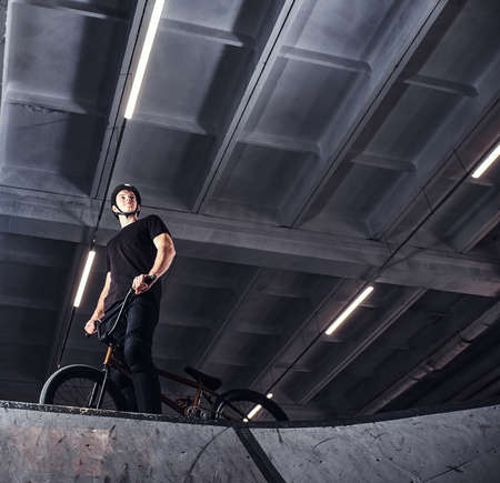 Professional BMX rider in protective helmet getting ready to jump in a skatepark indoors Stock Photo