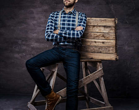 Old-fashioned man wearing a checkered shirt with suspenders with his arms crossed sitting on a wooden scaffolding