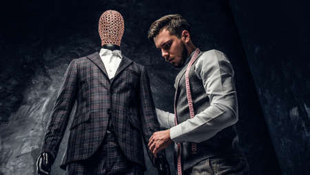 An elegantly dressed fashion designer working with custom made mens suit in a dark tailor studio