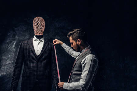 A young fashion designer with a measuring tape check the length of the sleeves of a custom made elegant mens suit in a dark tailor studio.
