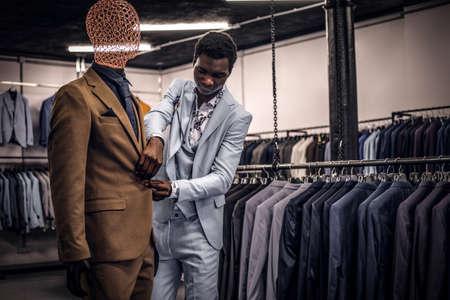 Un hombre afroamericano elegantemente vestido que trabaja en una tienda de ropa masculina clásica.