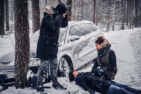 The girl witnessed the accident and provides first aid to the driver. The car got into a skid and crashed into a tree on a snowy road. 스톡 콘텐츠