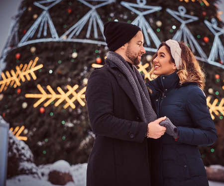 Happy young couple wearing warm clothes hold hands and look at each other, standing near a city Christmas tree, enjoying spending time together. Imagens