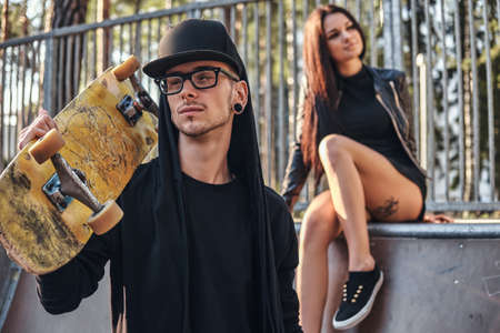 Stylish young couple in the skatepark at the summertime. Portrait of a skateboard in a hoodie and hat posing with a skateboard on the shoulder Archivio Fotografico