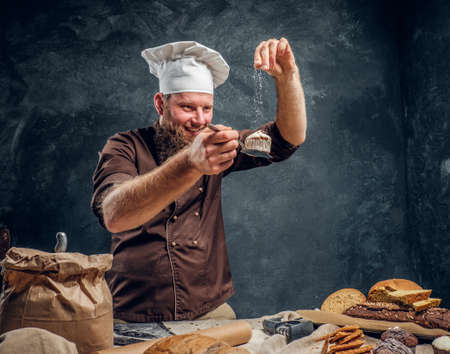 Cheerful bearded baker sprinkling some flour on his freshly made muffin next to a table in a dark studio 版權商用圖片