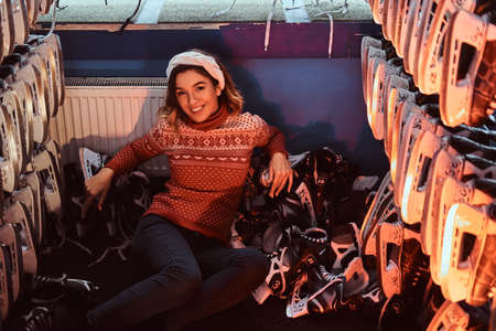 Cheerful young beautiful woman lying with a lot of ice skates in a locker room