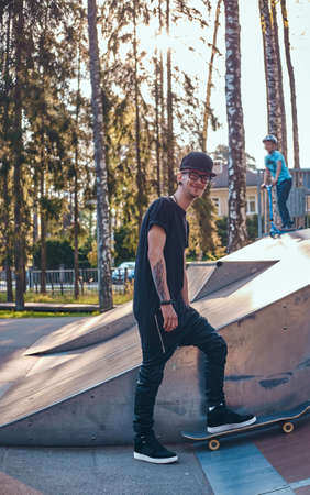 Young stylish skateboarder in a black shirt and cap standing on a board in the skatepark at the summertime Stock Photo
