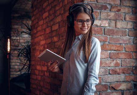 Smiling girl in elegant shirt holding a tablet enjoys favorite music in wireless headphones standing near brick wall Imagens