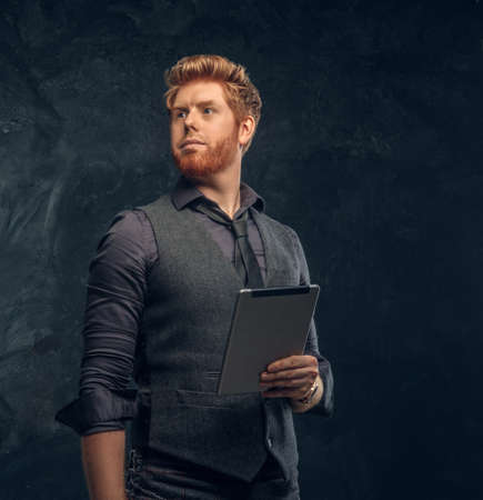 Handsome redhead man in formal wear holding a tablet in studio against a dark textured wall