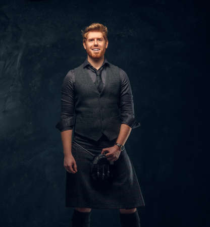 Happy redhead man dressed in an elegant vest with tie and kilt in studio against a dark textured wall Imagens