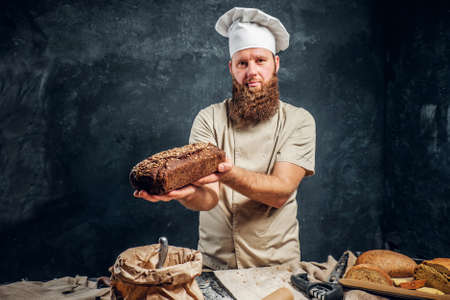 A bearded baker wearing a uniform showing fresh bread standing next to a table, decorated with delicious bread loaves, baguettes in a dark studio 版權商用圖片