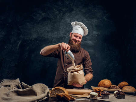 Cheerful bearded baker wearing a cook uniform sprinkling some flour in a bag, standing next to a table with delicious bread loaves, baguettes Stockfoto