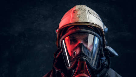 Brutal fireman in gas mask and helmet looks into camera on black background in studio