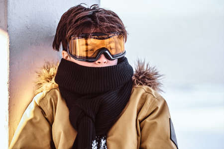 Portrait of a teenage snowboarder dressed in snowsuit and protective goggles sitting on railing near the snowy beach Imagens