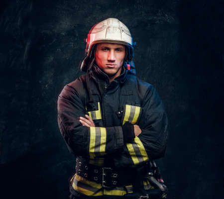 Brutal fireman in uniform posing for the camera standing with crossed arms and confident look. Studio photo against a dark textured wall