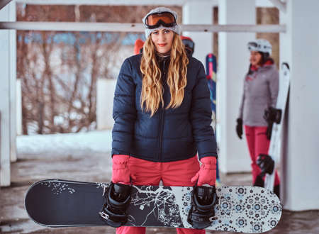 Charming Norwegian woman wearing warm clothes and goggles posing with a snowboard in the winter ski resort